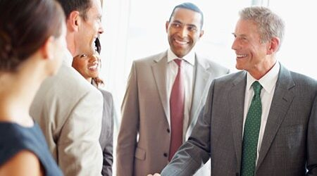 Business professionals shaking hands and smiling