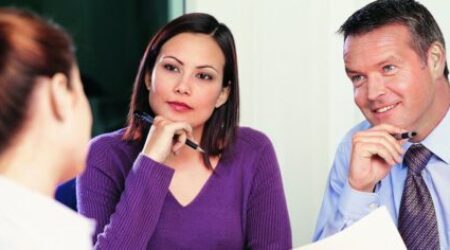 Professional woman and man interviewing a young woman for a job