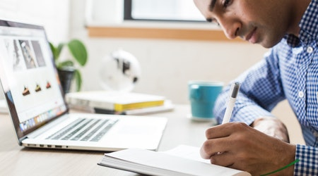 Young man working on a computer and taking notes