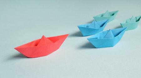 Multi-colored paper folded into origami boats.