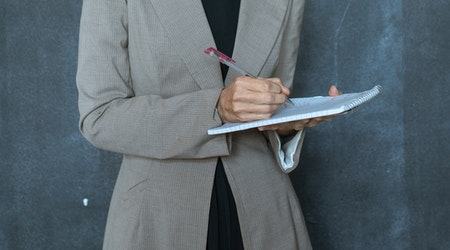 Woman taking notes with a pen and notebook