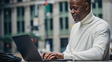 Mature man in a city typing on a laptop